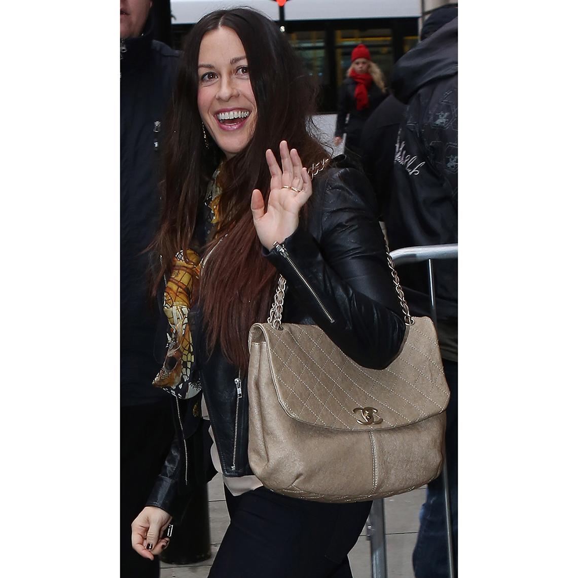 Alanis Morissette tucks a flap shoulder bag with chain strap under her arm.