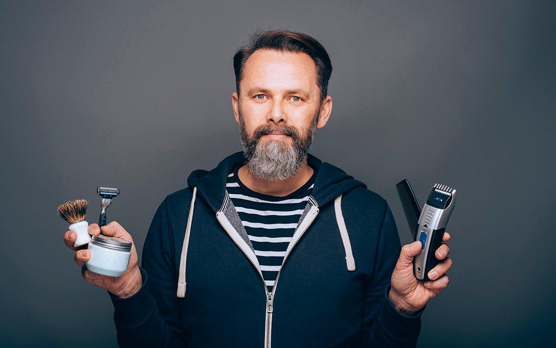 Hombre con barba y sosteniendo productos para su cuidado.