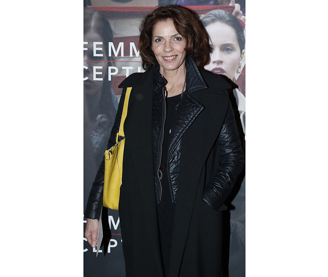 Elizabeth Bourgine wears a structured yellow shoulder bag over a black outfit
