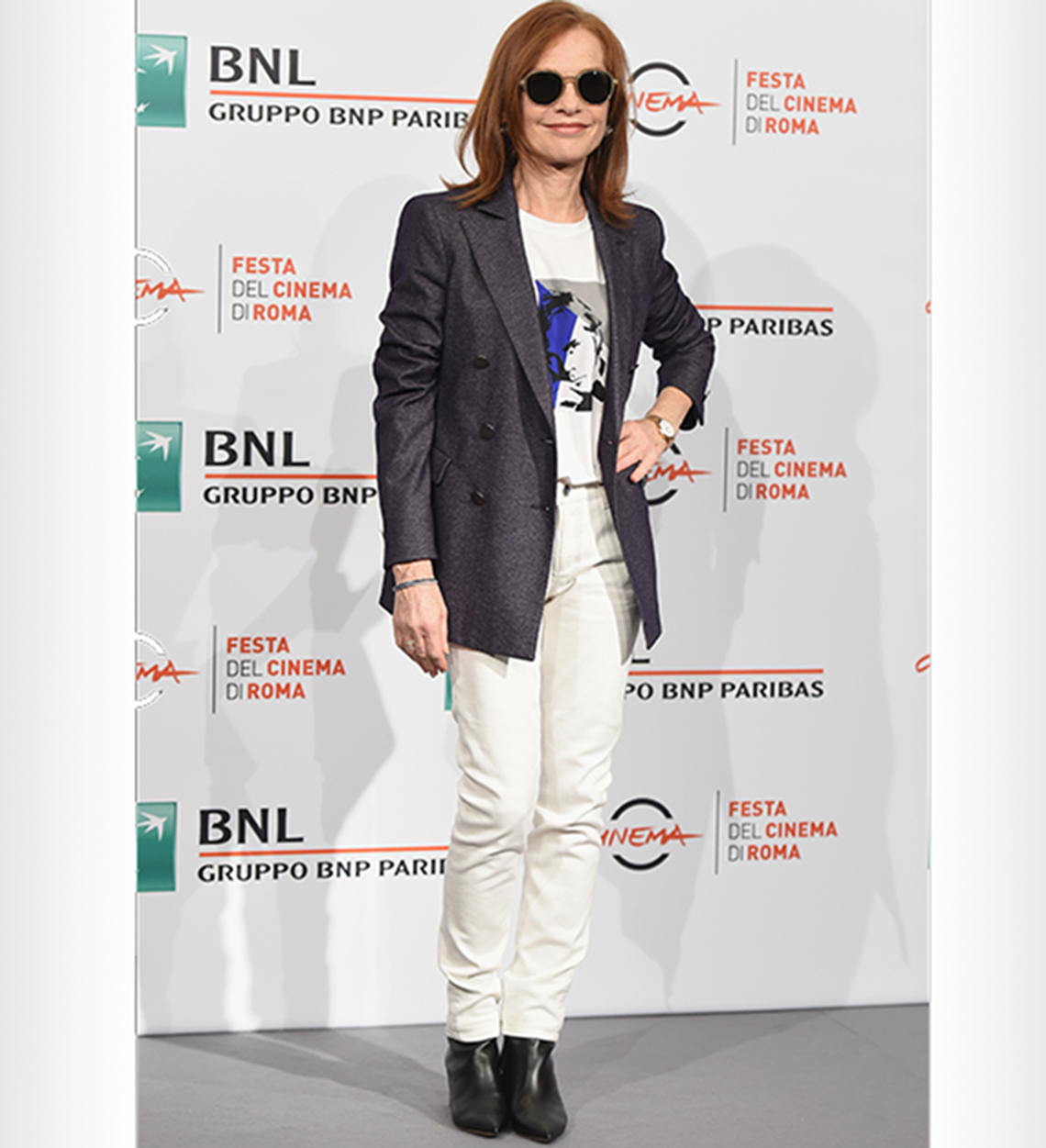 Isabelle Huppert in white jeans over black ankle booties with a blazer.