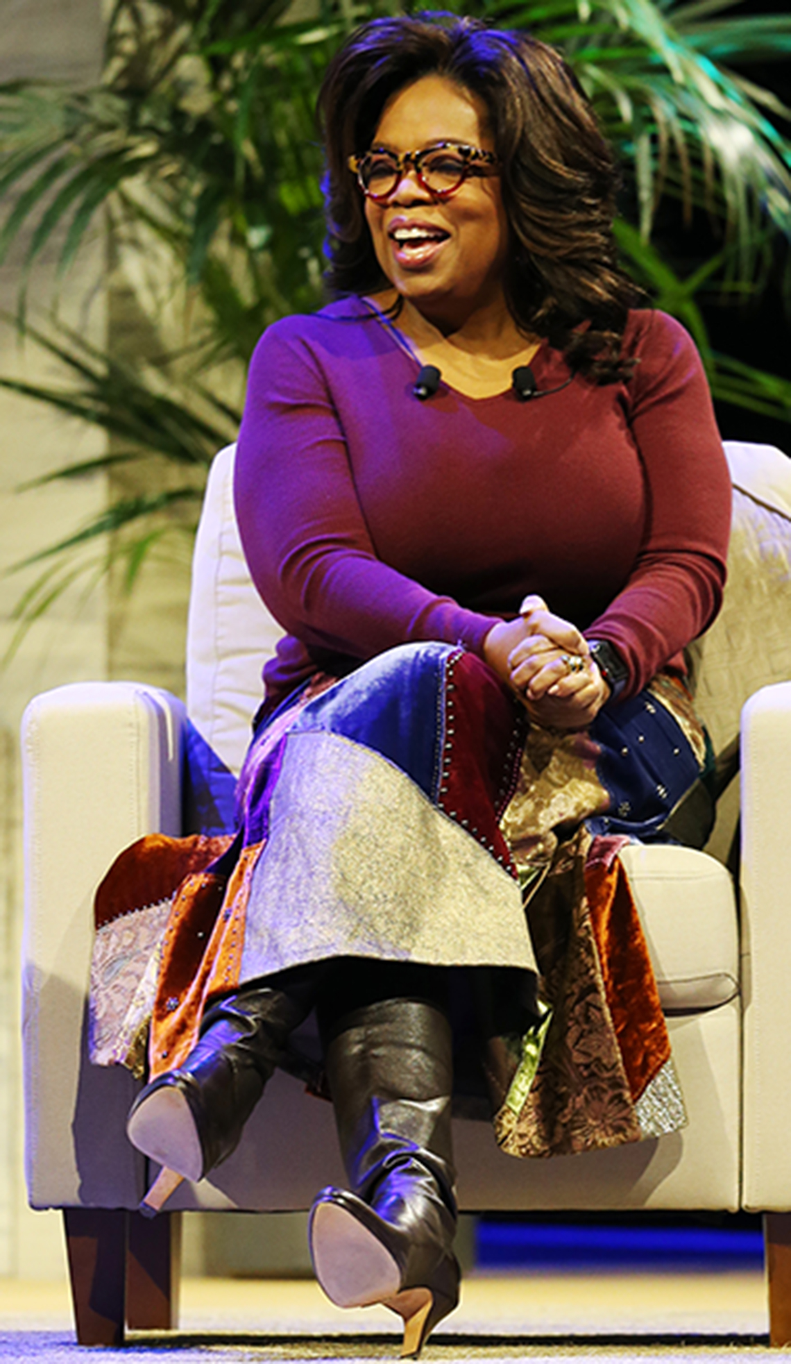 Oprah Winfrey in a long patchwork midi skirt and tall black leather boots.