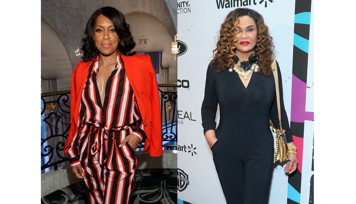 item 9, Gallery image. Regina King in striped red, black and white belt-tie, shirt-collar  jumpsuit with over-the-shoulders red blazer,  and Tina Knowles Lawson in black knit V-neck jumpsuit, a major statement necklace and metallic shoulder bag.