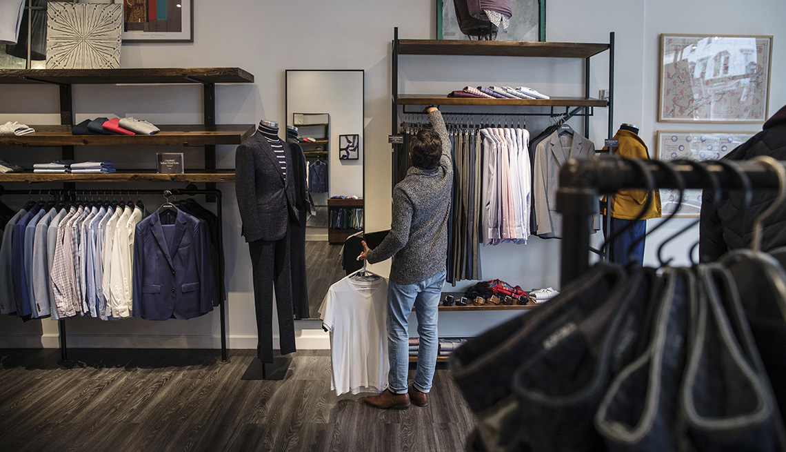 A salesperson arranges clothes in a Bonobos