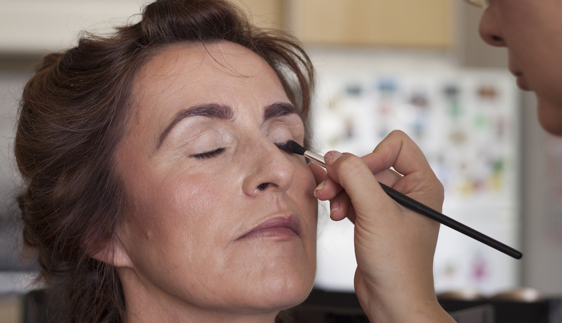 Mature woman having make-up applied by make-up artist