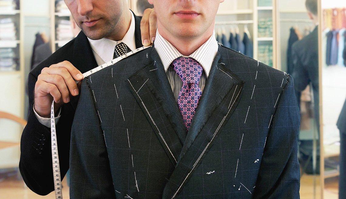 Hombre es medido por un sastre para un traje