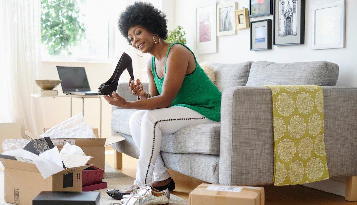Mujer sosteniendo un zapato de tacón en la sala de su casa.