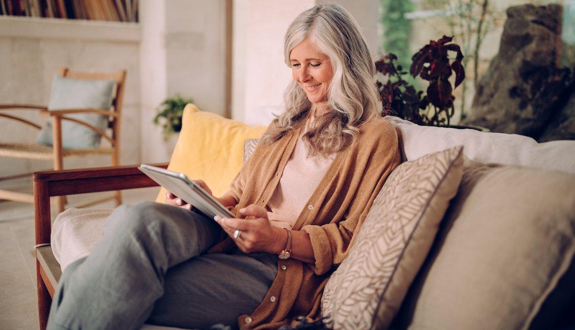 Mujer sentada en un sofá y mirando una tableta.