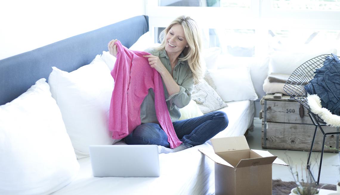 Mujer en un sofá viendo una blusa de color rosado.