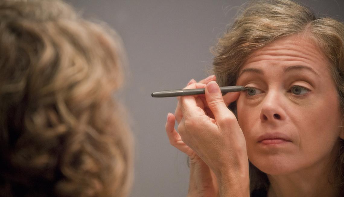 Caucasian woman applying eyeliner in mirror