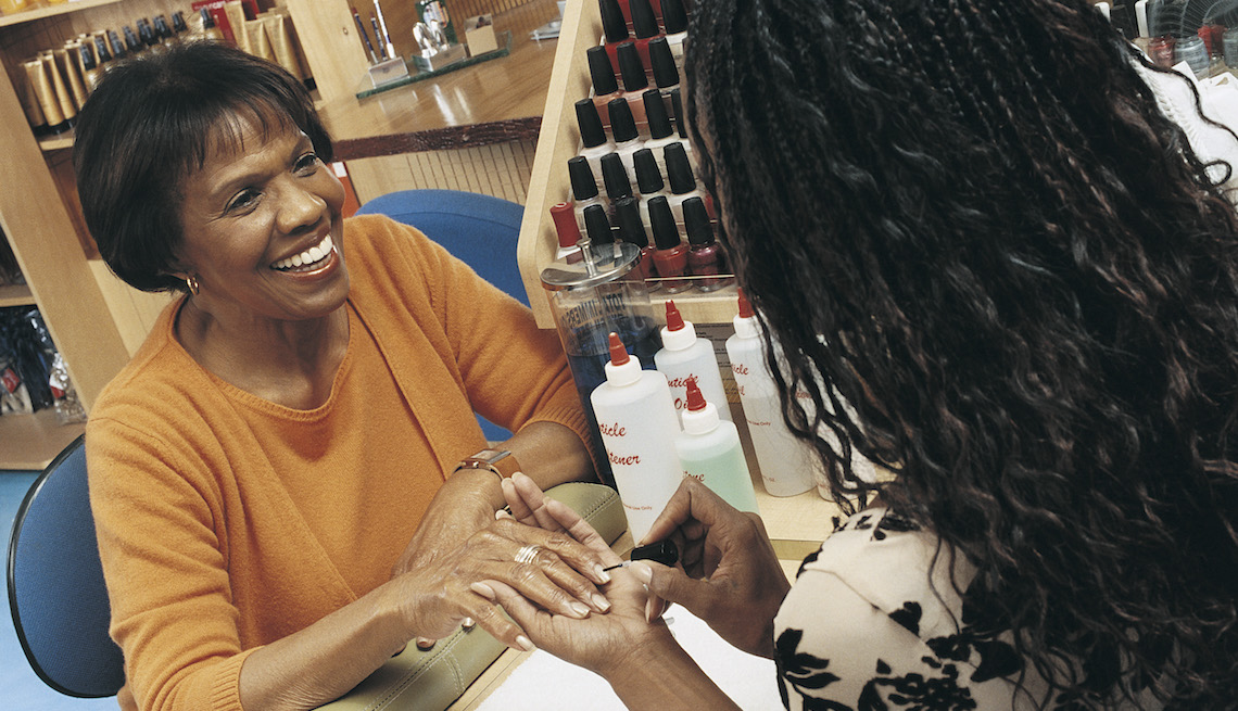 Smiling Woman Having Her Nails Manicured in a Beauty Salon