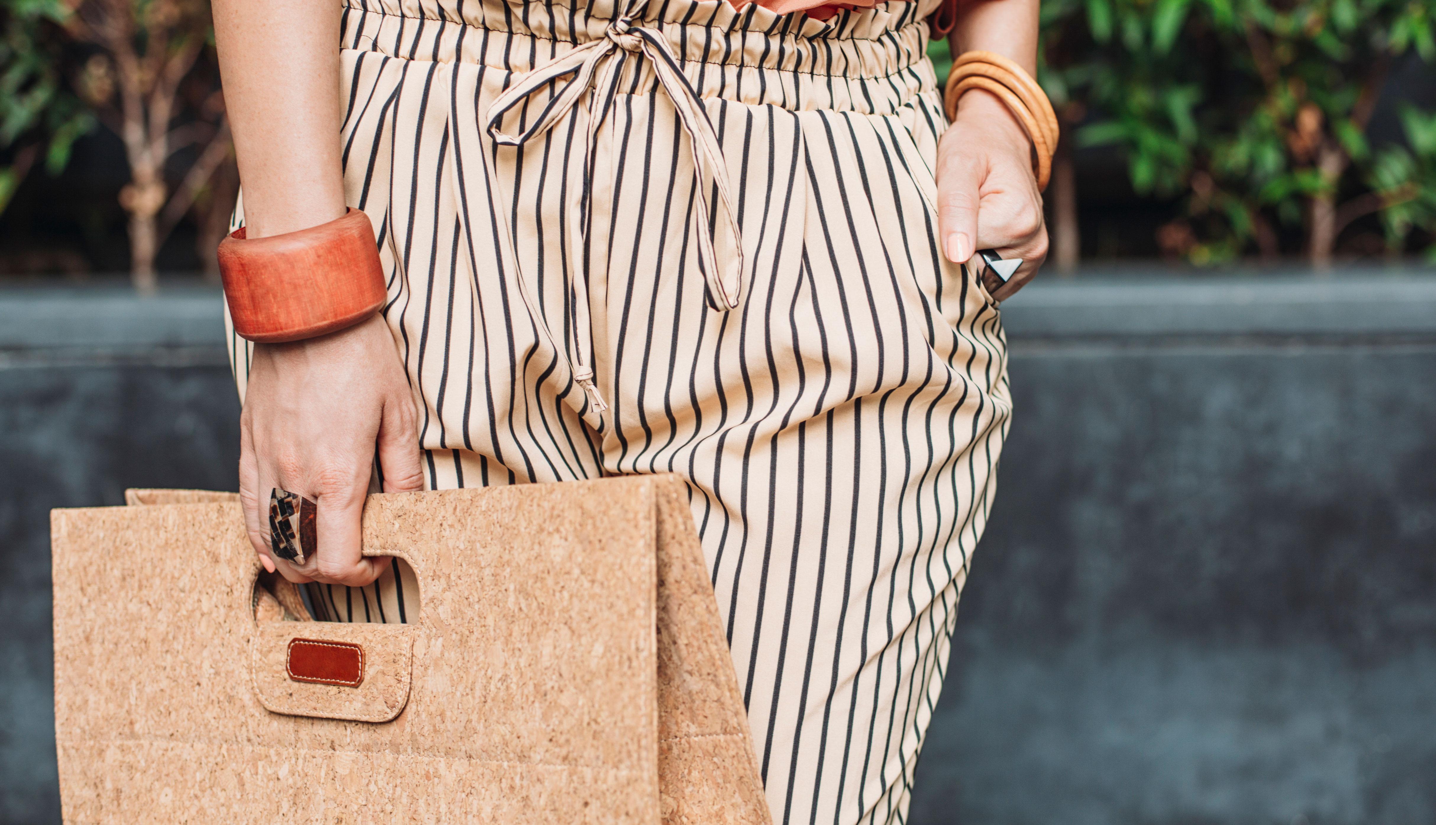 Mujer vistiendo tonos beige y con cartera en mano