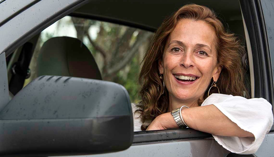 Mature woman smiling looking at the camera sitting in her car