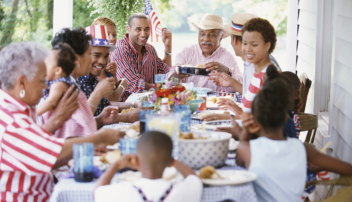 item 2 of Gallery image - Multi-generation Black family eating at Fourth of July barbecue
