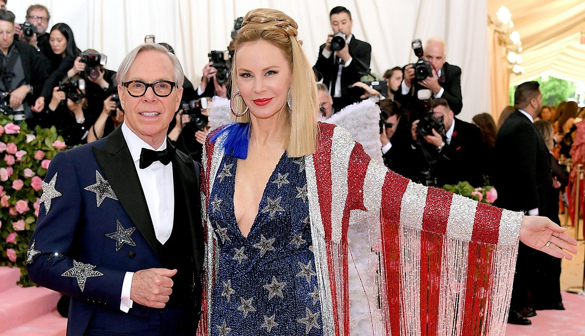 item 1, Gallery image. Tommy and Dee Hilfiger at the Met Gala: Tommy in star studded navy tux, Dee in navy star studded gown with red and white striped shawl