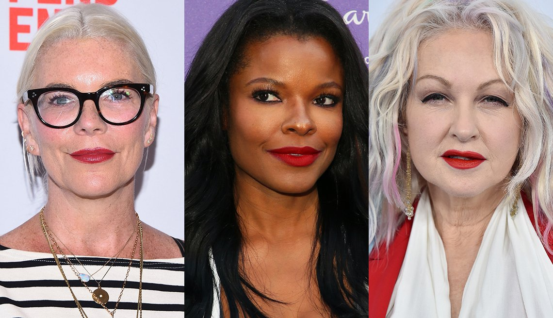 item 3, Gallery image. Wren Arthur in red lips, striped T-shirt and bold black glasses; Keesha Sharp in a bold red matte lipstick;  Cyndi Lauper in platinum hair, red lips, red tailored jacket, white scarf