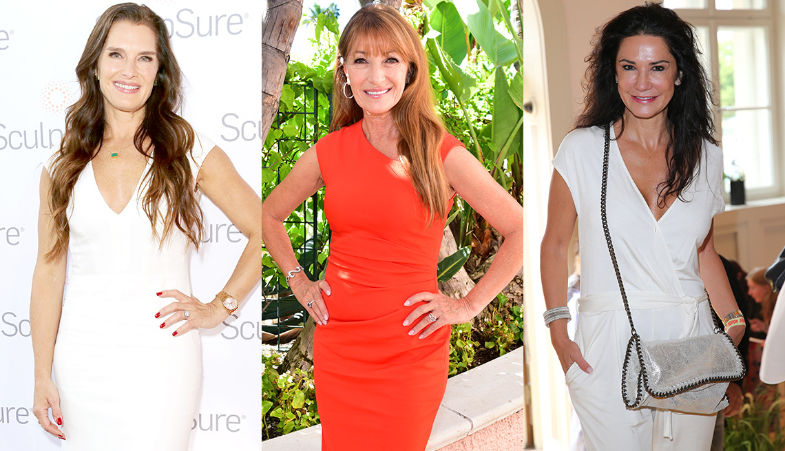 item 4 of Gallery image - Brooke Shields in a white V neck sheath dress with extended cap sleeve, deep V neck; Jane Seymour in extended shoulder high neck red sheath dress with bare arms; Mariella Ahrens in white cap sleeve jumpsuit