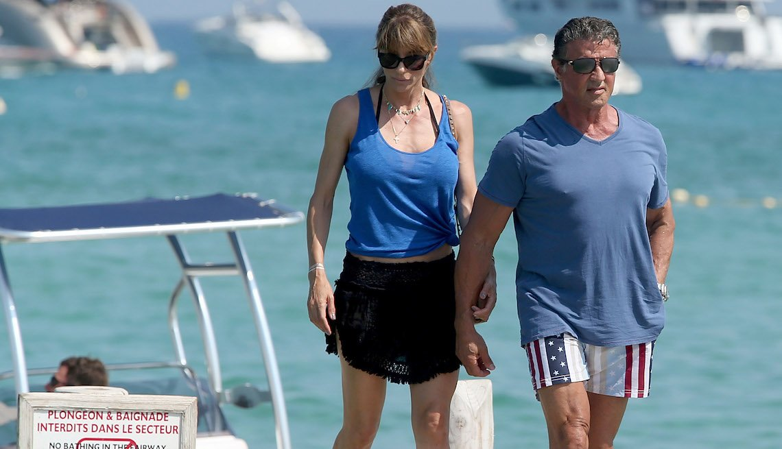 item 1, Gallery image. Sylvester Stallone in stars and stripes shorts, a gray-blue T-shirt and black kicks; Jennifer Flavin in a blue tank, black ruffled mini wrap over a halter bikini.