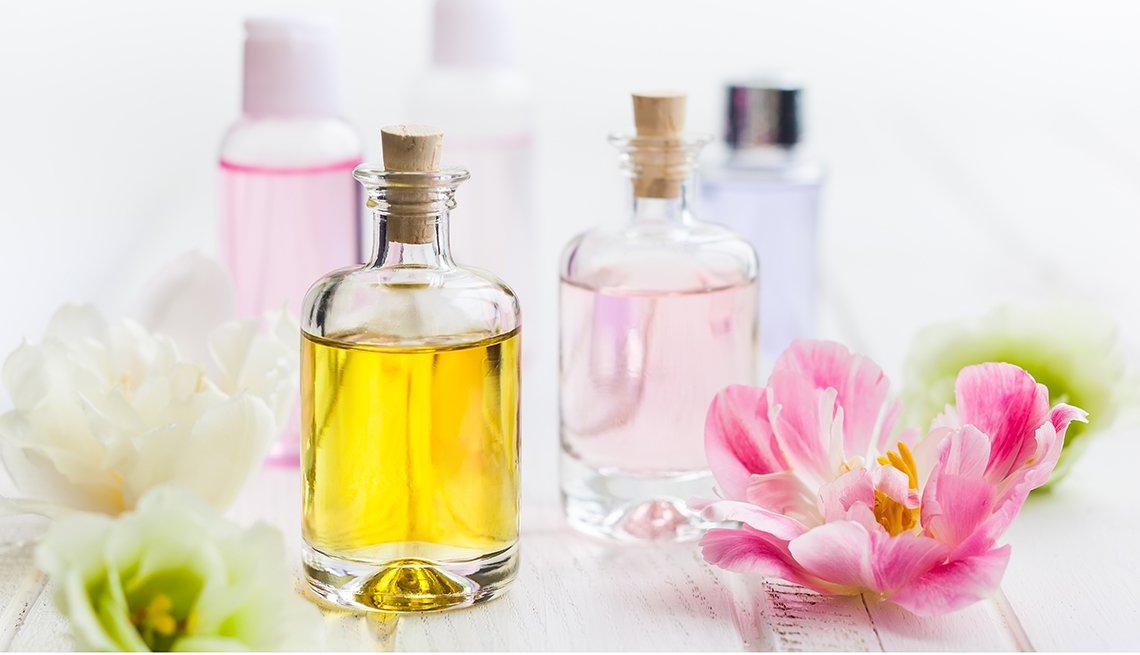 Frascos de vidrio con aceites faciales con unas flores a los lados.