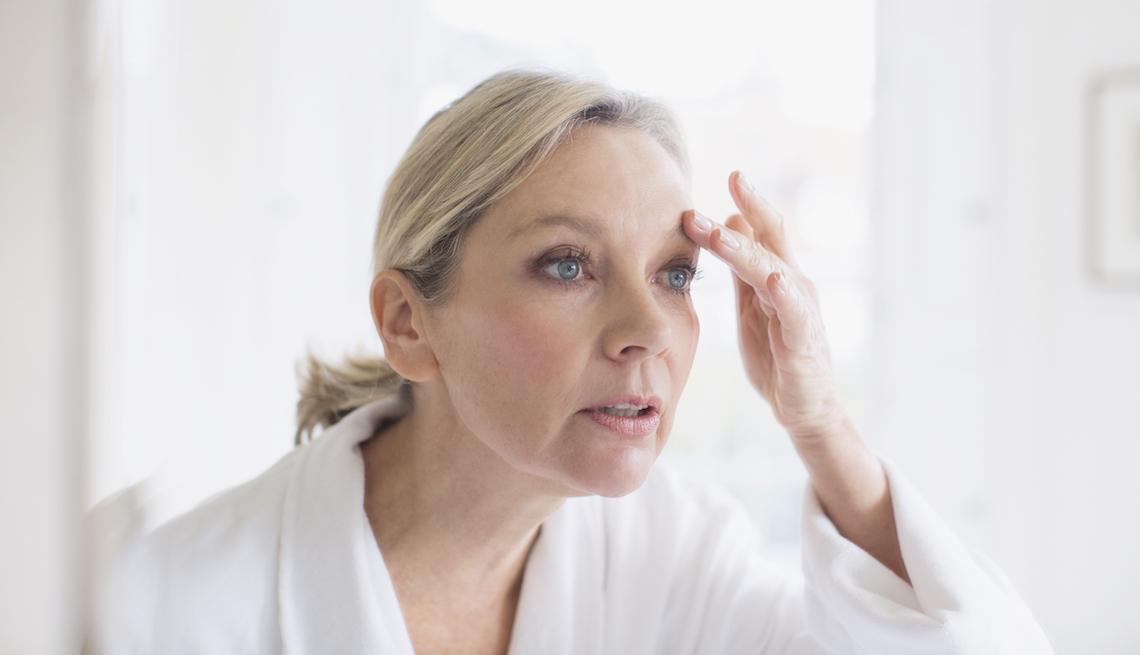 item 10 of Gallery image - Mujer adulta tocándose las cejas frente a un espejo en un baño.