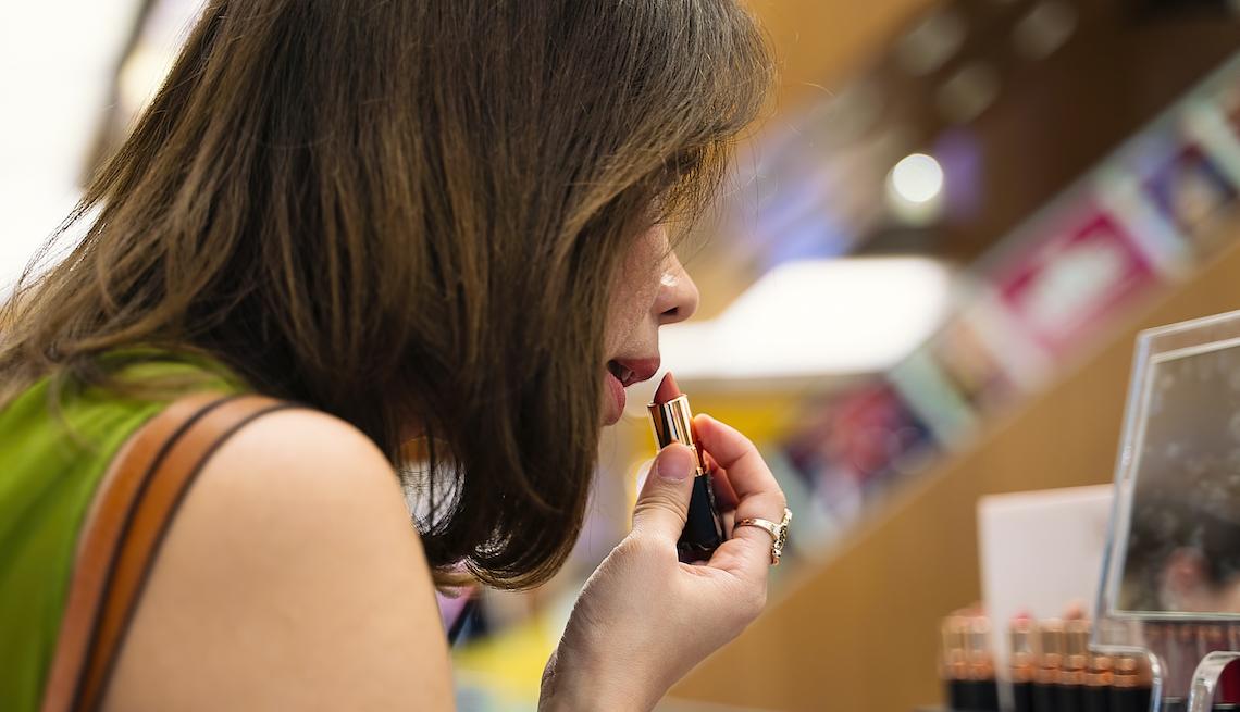 item 9 of Gallery image - Mujer usando un pintalabios frente a un espejo.