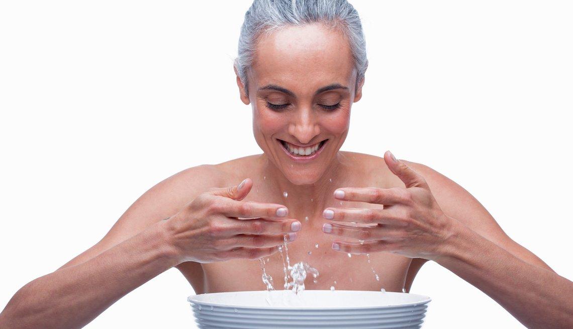 Mujer mayor se lava la cara.