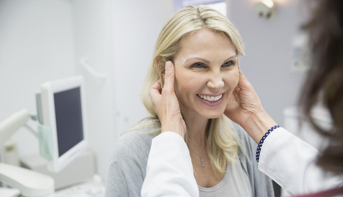 item 1 of Gallery image - Mujer con una cirujana plástica en su consultorio mientras la examina.