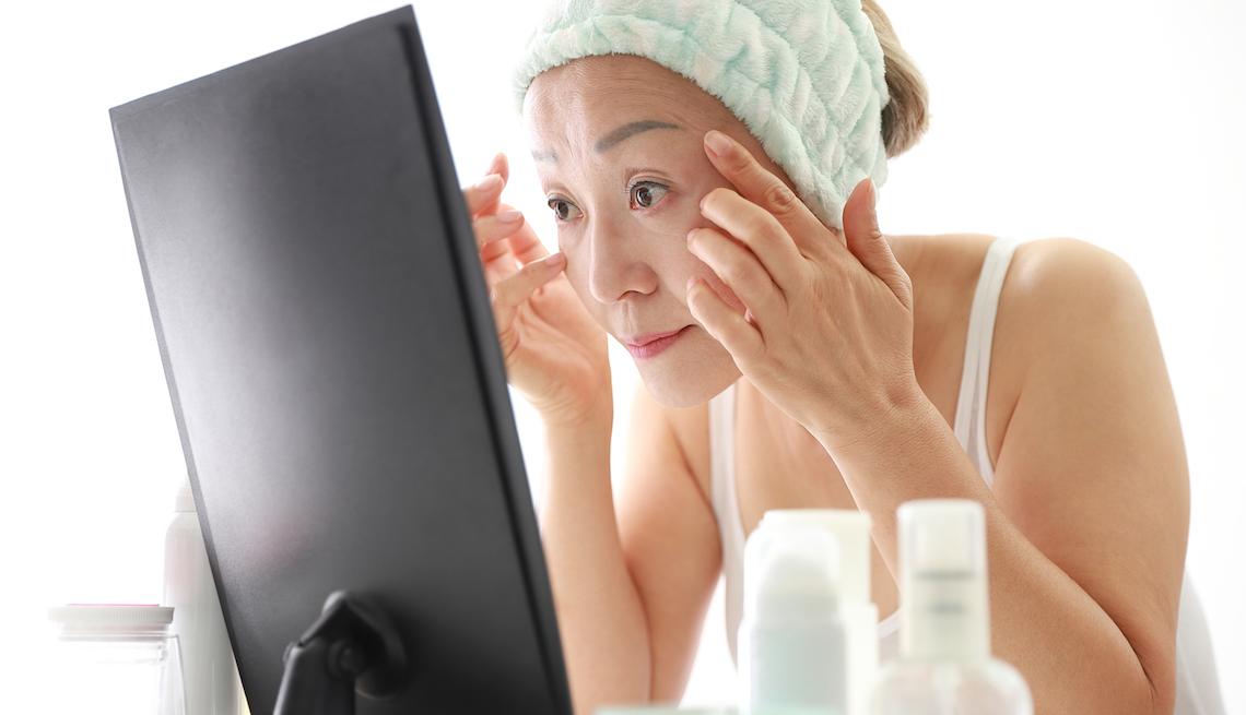 item 12 of Gallery image - Mujer mayor mirándose las arrugas frente a un espejo.