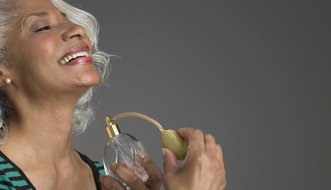 item 3 of Gallery image - Mujer mayor usando un perfume sobre su cuello.