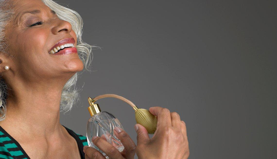 item 3, Gallery image. Mujer mayor usando un perfume sobre su cuello.