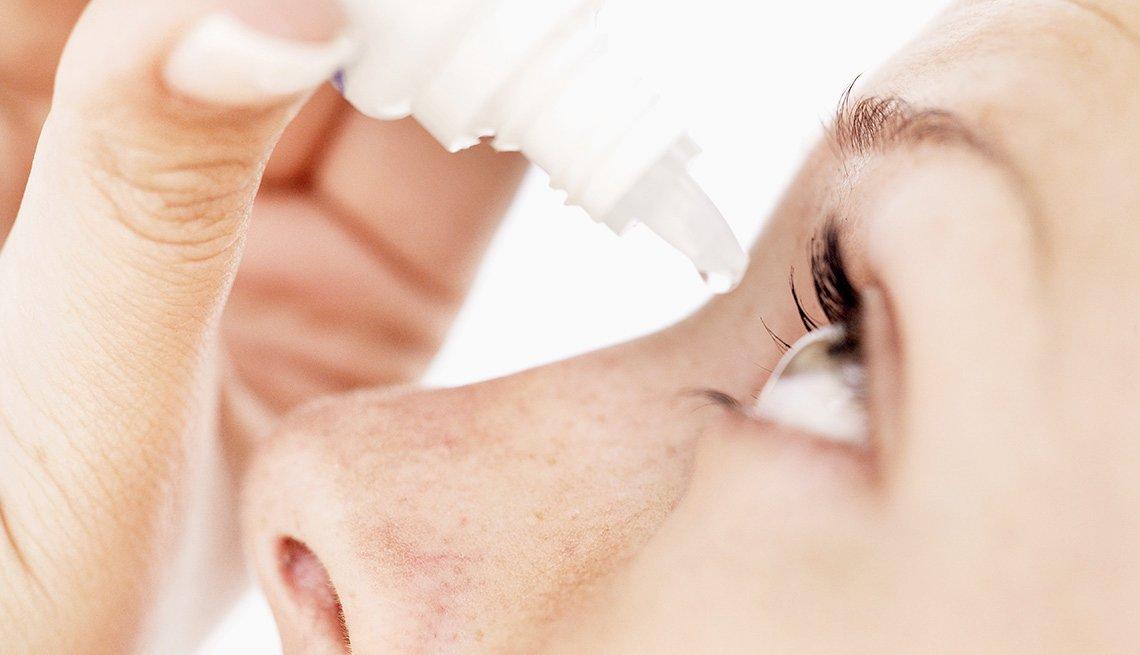 Mujer aplicando gotas para los ojos.