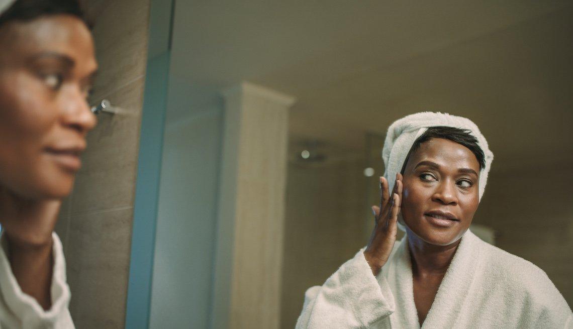 Mujer mayor vestida con salida de la ducha se toca la cara y se mira en el espejo del baño.