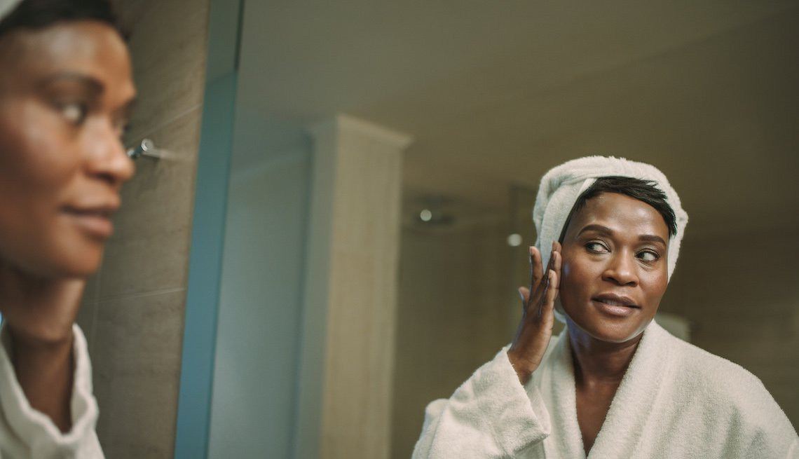 item 11, Gallery image. Reflection of mature woman in bathroom mirror applying cosmetic cream on her face. Mature female in bathrobe putting on cream on her face skin.