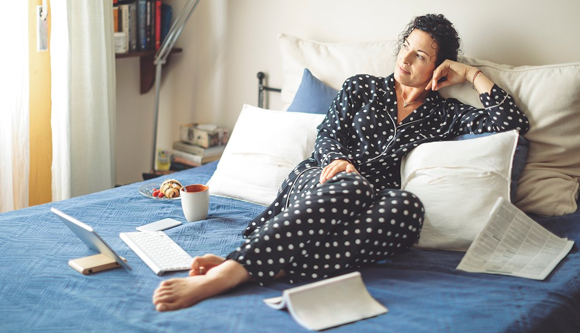A woman in black and white polka dot pajamas lying in bed