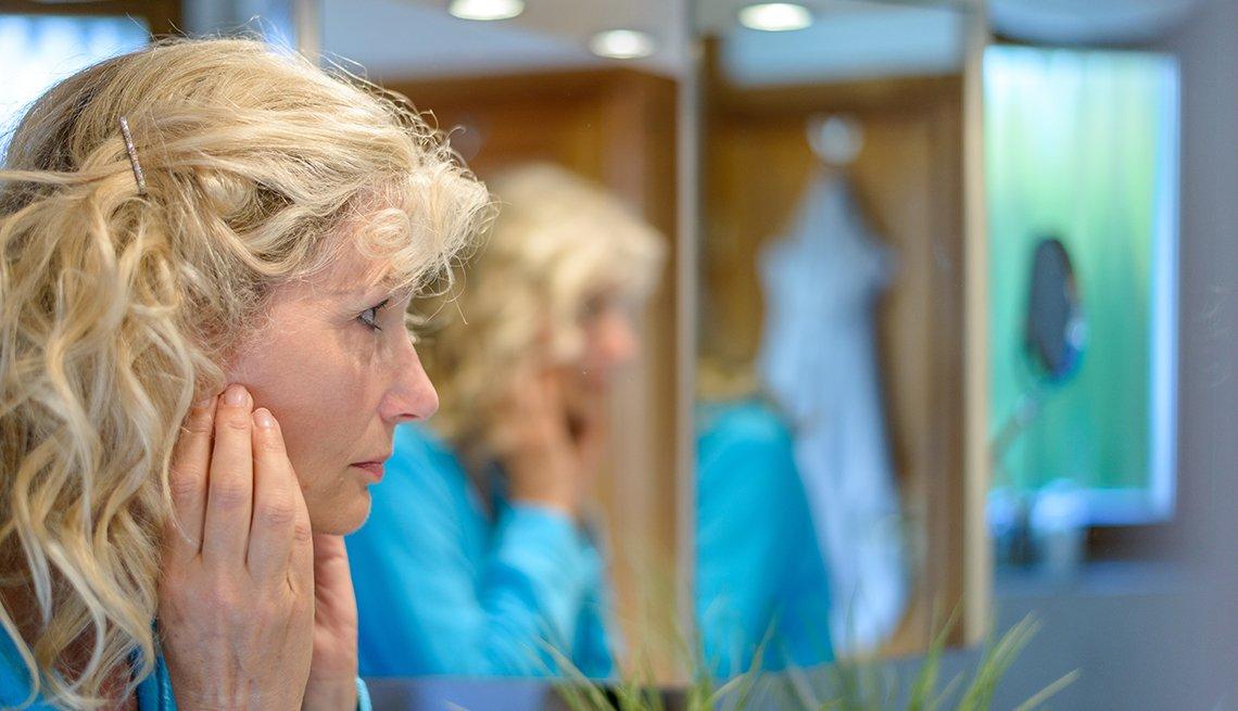 Mujer con sus manos en la cara mirándose en un espejo.
