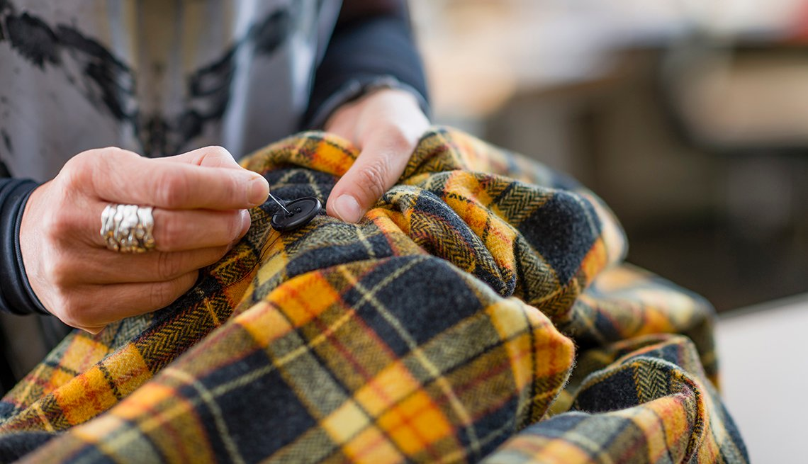 A close up of a woman hand sewing a button onto a jacket
