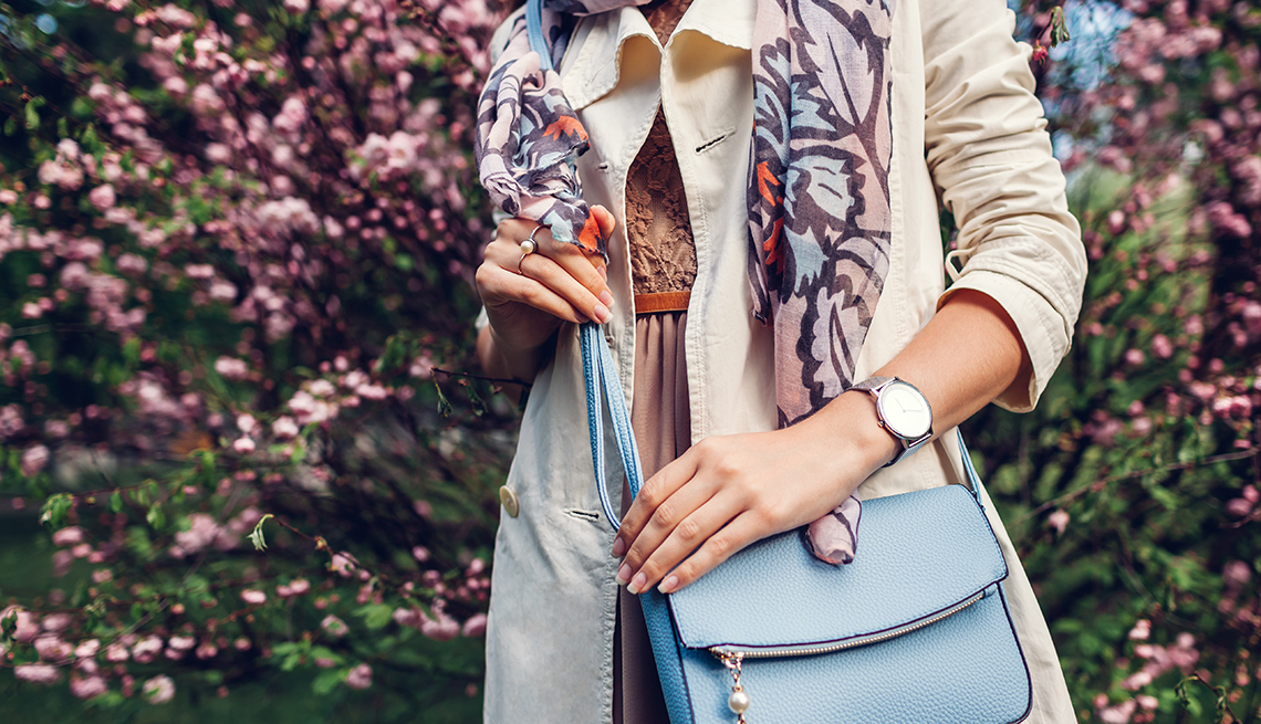 A woman holding a stylish blue handbag and wearing trendy outfit in a garden