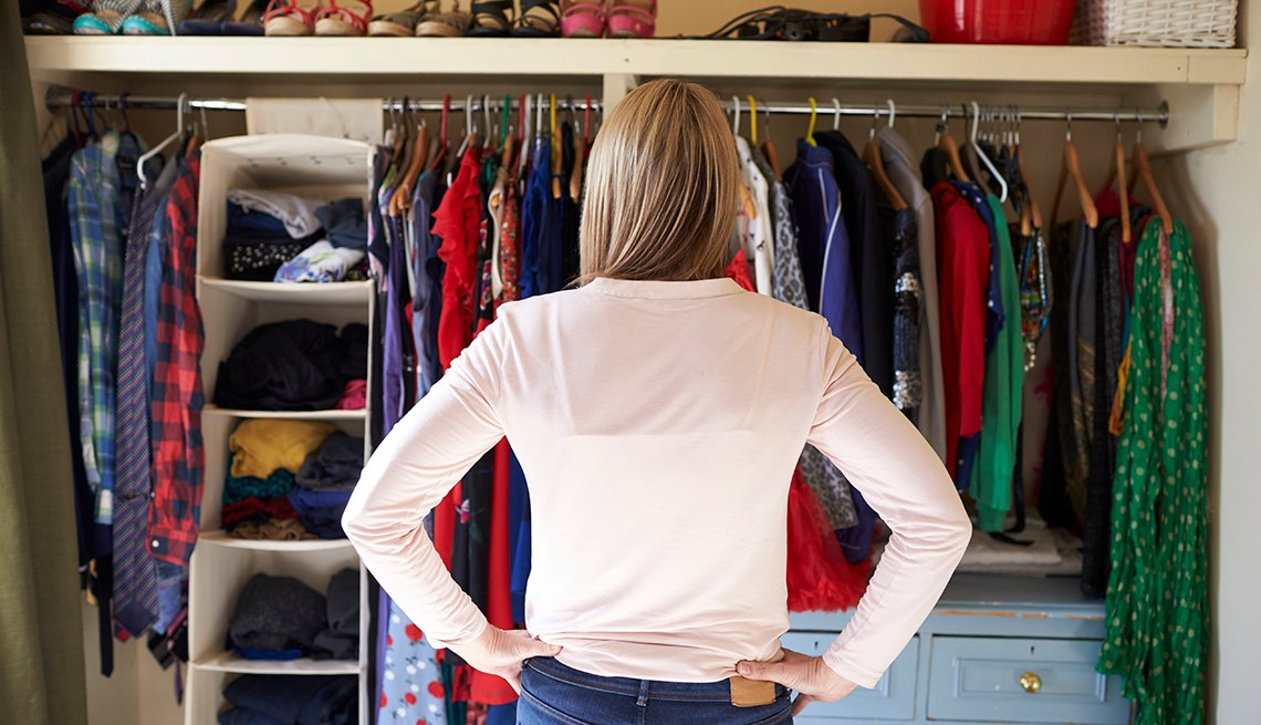 A woman in her bedroom looking at clothes and shoes in the closet