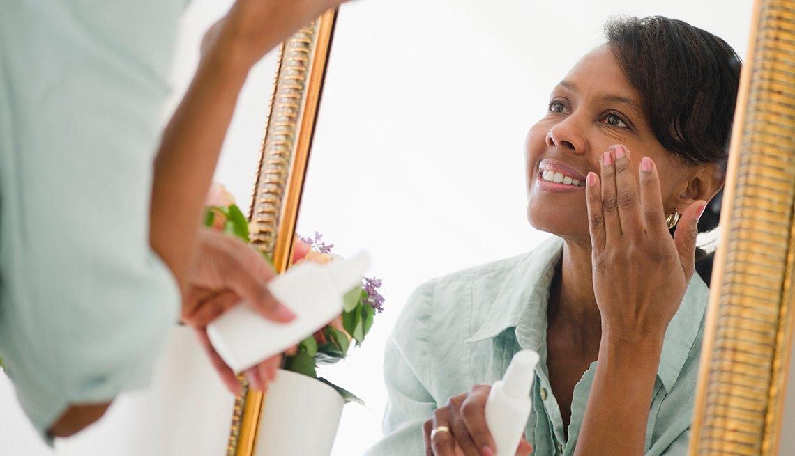 Mujer mirándose en un espejo mientras se aplica una crema en la cara.