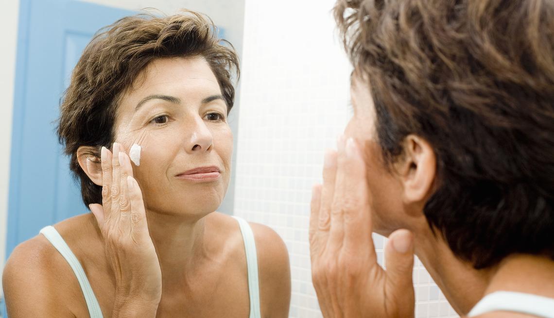 item 1 of Gallery image - Mujer mirándose en un espejo mientras se aplica una crema en la cara.
