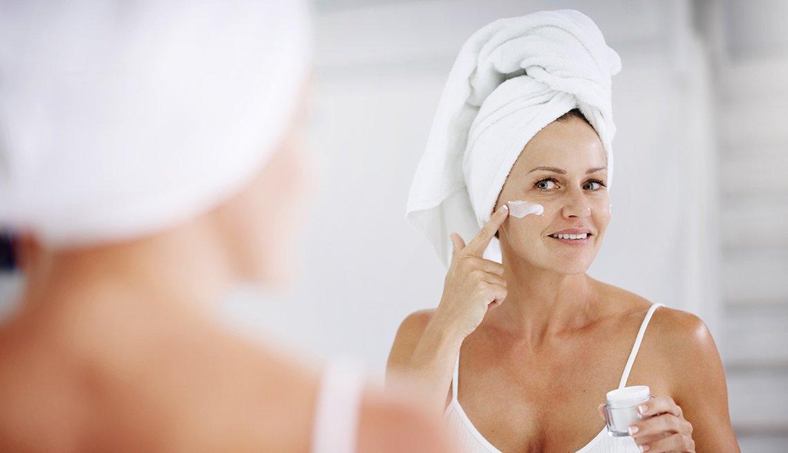 item 4 of Gallery image - Mujer mirándose en un espejo mientras se aplica una crema en la cara.