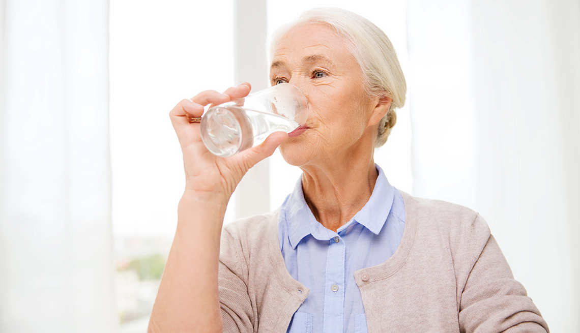 item 5 of Gallery image - A woman drinking a glass of water at home