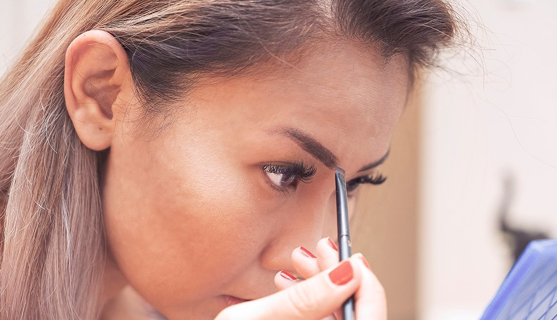 item 1 of Gallery image - A woman filling in her eyebrows with an eyebrow brush