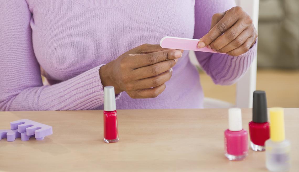 Manos de una mujer mientras se arregla las uñas.