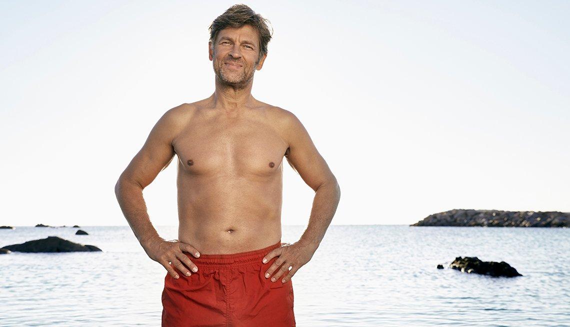 Un hombre usando una pantaloneta de baño con el mar al fondo.