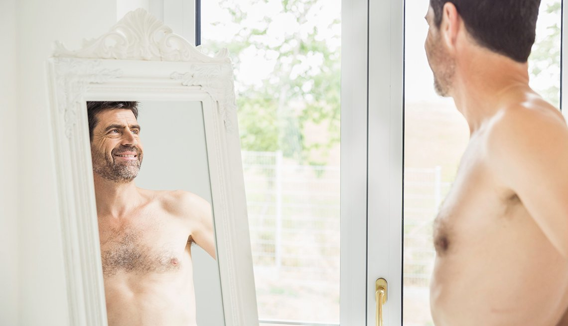 item 1 of Gallery image - A shirtless man looking at himself in a full length mirror at home