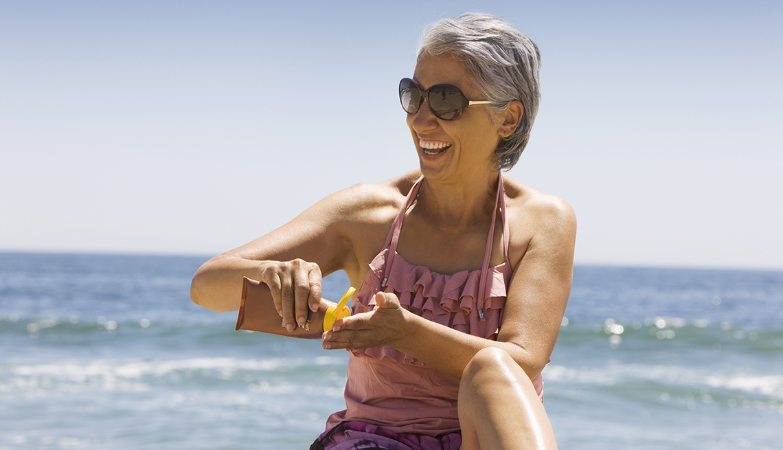 A woman applying sunscreen at the beach