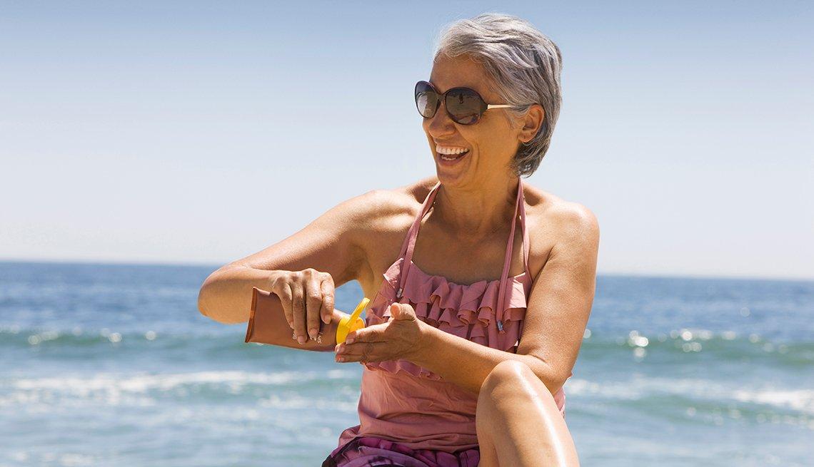 A woman applying sunscreen at the beach