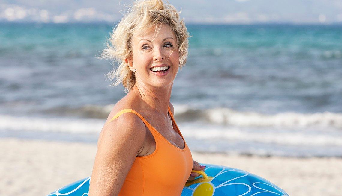 Mujer en una playa sosteniendo un flotador.
