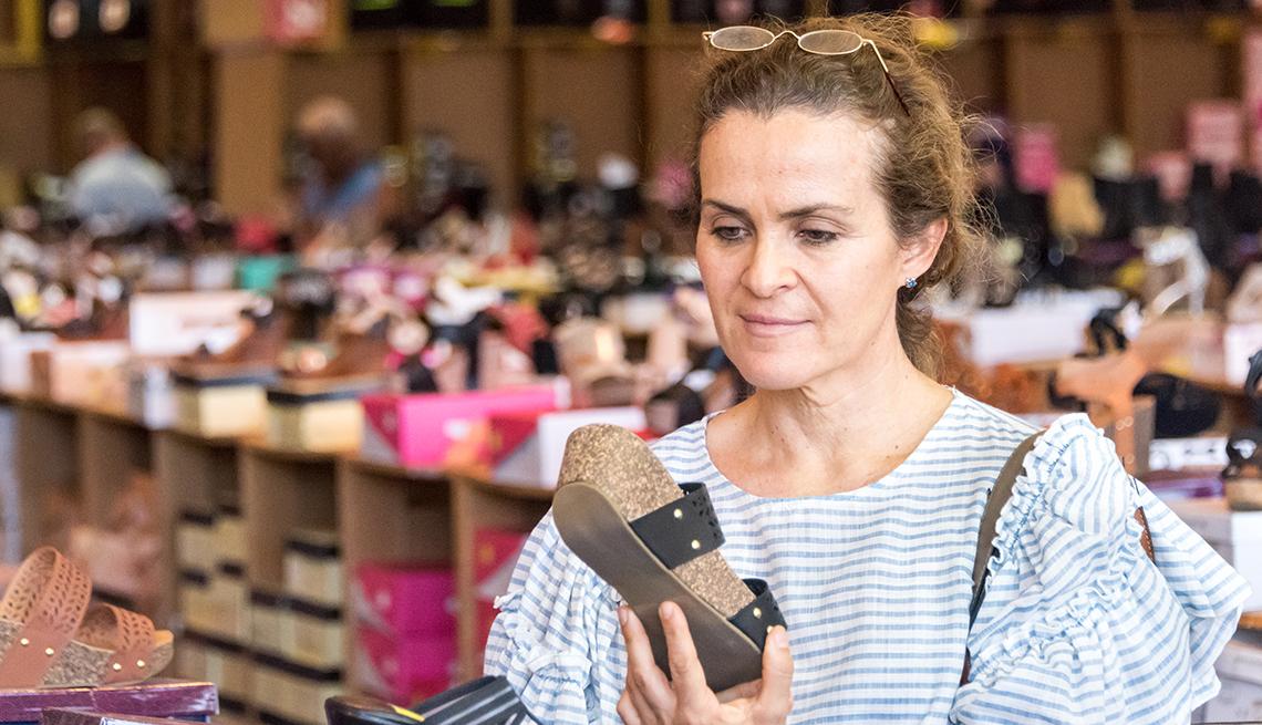Mujer mirando zapatos de verano en una tienda.