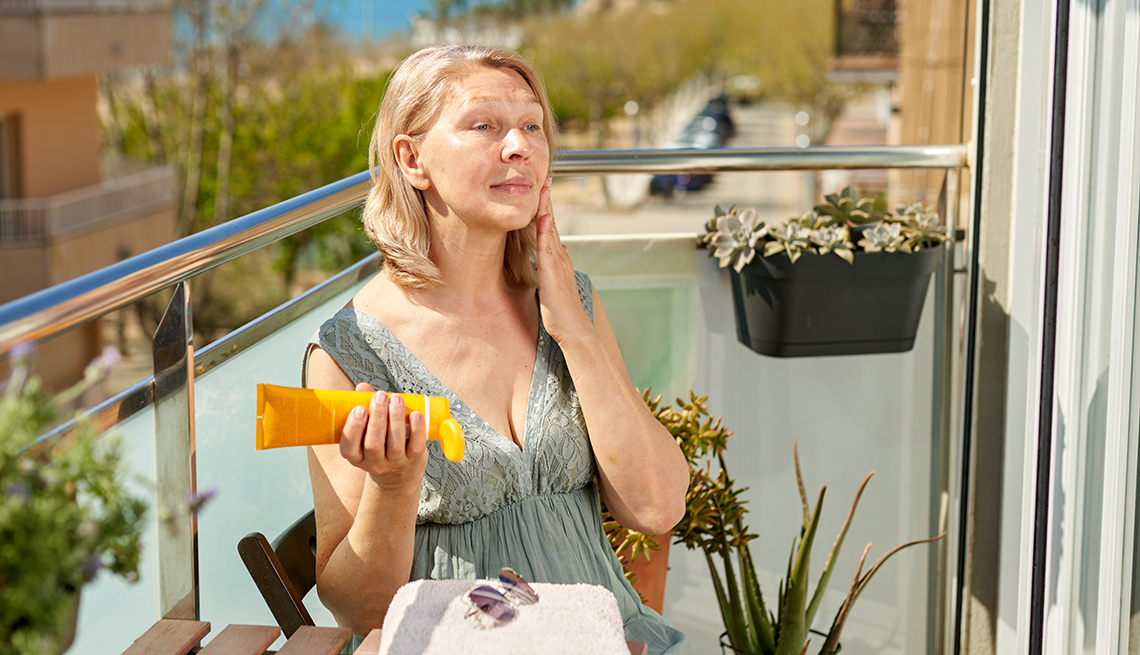 item 9 of Gallery image - A woman applying sunscreen on her face on a hotel terrace